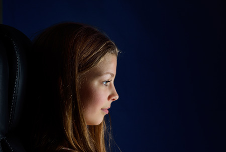 blonde teenage girl: A blonde teenage girl is sitting in the armchair in darkness. She is sad or serene. She is photographed in the dark with few highlights. Stock Photo