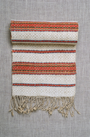 convolute: Ukrainian rushnyk is decorated with red stripes and fringe. It is rolled.