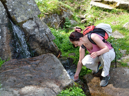 streamlet: A happy woman is scooping up water in the small stream on the tourist pathway.