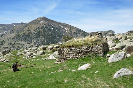 hutch: A tourist is taking photo the handmade hutch on the green slope in the upper part of the Vall-de-Madriu-Perafita-Claror.