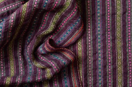 homespun: The vintage homespun wool textile with various vertical colored stripes is crumpled and photographed closely.