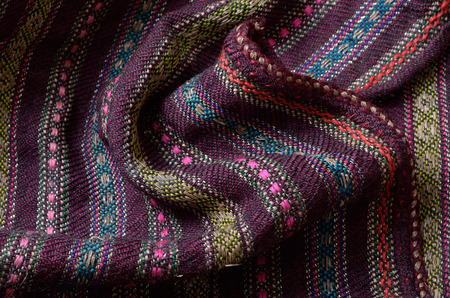 homespun: The vintage homespun wool textile with various colored stripes is crumpled and photographed closely.
