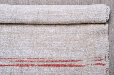 homespun: Hemp homespun cloth is decorated with red stripes. It is rolled and photographed closely.