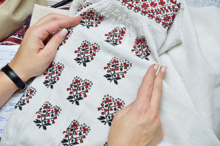 embellished: Female hands hold the homespun linen sleeve embellished with black and red  embroidery.