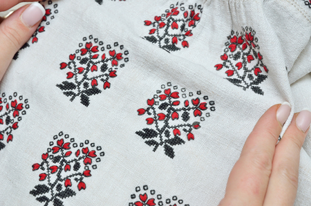 homespun: Female hands hold the homespun linen sleeve embellished with black and red embroidery.