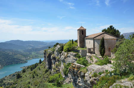 extant: The antique church is extant in the old small village on the bluff cliff under the valley in the Prades Mountains. Foto de archivo