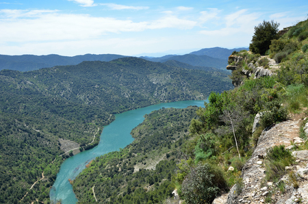 forested: Prades mountains is a large calcareous mountain massif forested. There are the river Embalsa with the artificial lake in the green valley.