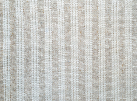 homespun: Linen homespun fabric is decorated with white stripes. It is photographed closely.