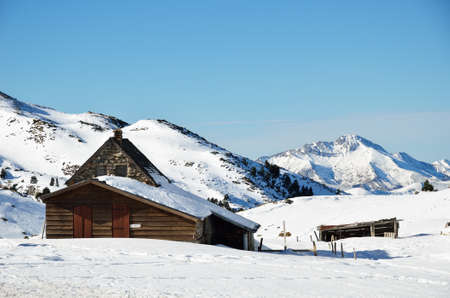 outbuilding: A solitary small stone house with an wood outbuilding is on the mountain slope covered by snow. Stock Photo