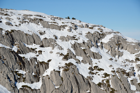 abrupt: Gray limestone steep cliff is slightly covered with white snow in the French Pyrenees.