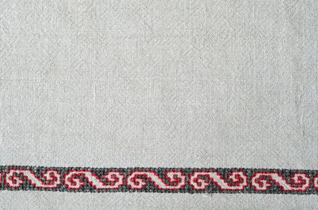 punto de cruz: La tela de andar por casa blanca decorada con bordados hechos a mano a lo largo del borde inferior. El patrón de color rojo y negro se hace por la cruz-puntada. Foto de archivo