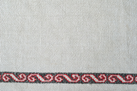 punto de cruz: The white homespun cloth is decorated with handmade embroidery along the bottom edge. The red and black pattern is made by cross-stitch.