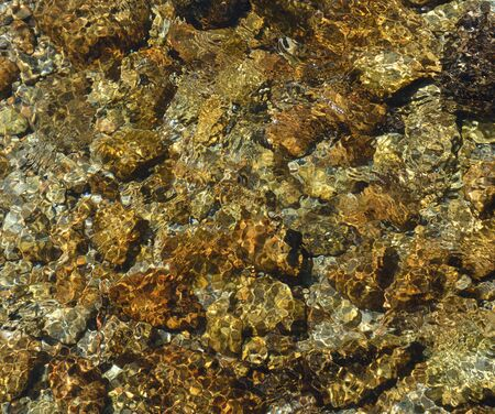 wavelet: Vibrant colored rocks are seen through the clear water flowing. The mountain river of Andorra is known for its transparent water. Stock Photo