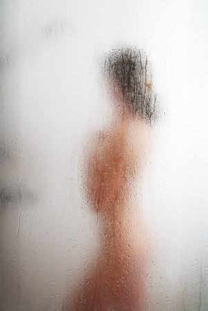 A nude young woman is washing in the shower bath. Her blurred silhouette is visible through the sweat glass surface with water drops and streams. Focus is on the wet glass wall of the shower cabin. photo