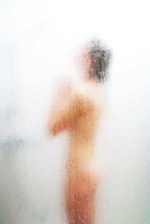 Female blurred silhouette is visible through the sweat glass surface with water drops and streams. A nude young woman is washing in the shower bath. Focus is on the wet glass wall of the shower cabin. photo
