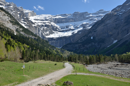 cirque: The pathway goes along the valley to falls in the cirque of Gavarnie. In the background there is a large rock amphitheater in the French Pyrenees. Stock Photo