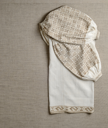 homespun: The vintage Ukrainian shirt on the homespun linen fabric Stock Photo