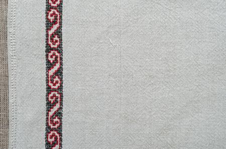 punto de cruz: La tela de andar por casa blanca decorada con bordados hechos a mano a lo largo del lado izquierdo. El patr�n de color rojo y negro se hace por la cruz-puntada. Foto de archivo
