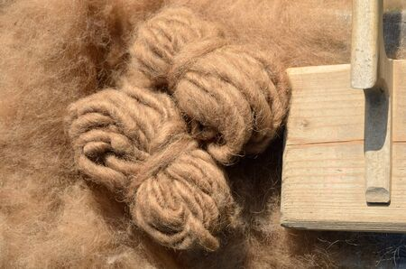 manually: Two skeins of the manually spun yarn and a wooden tool are on the sheeps fleece. Stock Photo