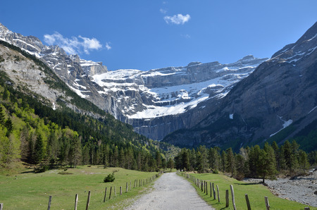 cirque: The pathway goes along the valley to falls in the cirque of Gavarnie. In the background there is a famous rock amphitheater in the French Pyrenees. Stock Photo