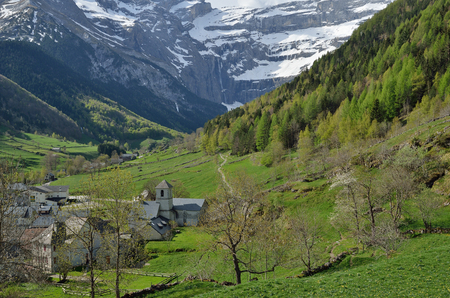 abrupt: Gavarnie is a small village in the mountain valley of the river Gave de Pau. In the background there is a famous rock amphitheater. There are a lot of waterfalls, snowfields and glaciers. Stock Photo