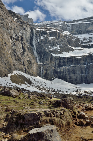 overhang: The cirque de Gavarnie is a large rock amphitheater. The cirques walls are twisted and layered. There are a lot of waterfalls and steep walls. Stock Photo