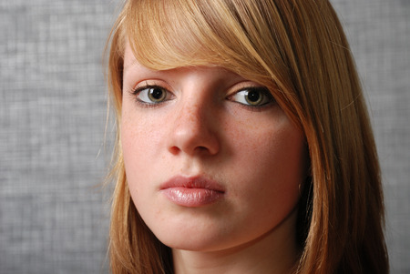 girl face close up: A teenage girl is looking at the camera calmly. She is natural blonde with a fringe and freckled skin. Her face is photographed closely.