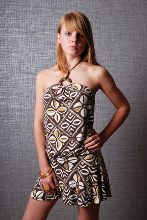 cocktail dress: A teenage girl is standing and looking seriously at the camera. She is wearing a cocktail dress. Stock Photo