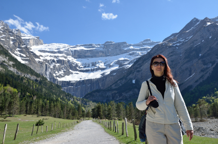 cirque: A woman goes in the hiking trail to falls of the cirque of Gavarnie. In the background there is a famous rock amphitheater in the French Pyrenees. Stock Photo