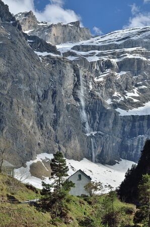 hollow walls: The cirque de Gavarnie is a large rock amphitheater. The cirques walls are twisted and layered. There are a lot of waterfalls and steep walls. Stock Photo