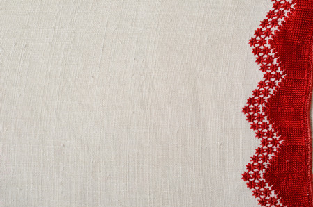 homespun: The white homespun cloth is decorated with handmade embroidery along the right side. The red pattern is made by pearl stitch. This is a traditional Ukrainian kind of satin stitch. Stock Photo