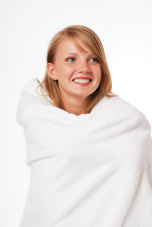 look pleased: Pretty woman is wrapping herself warm in the large white towel. She feels comfortable. She is smiling.