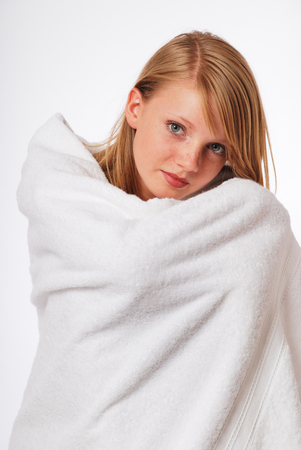 look pleased: Pretty woman wrapped herself warm in a bath towel. She feels comfortable. She is looking at the camera.