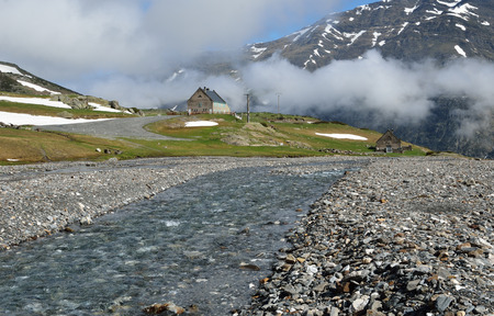 rapidly: The mountain stream is rapidly flowing on the stone bed from the cirque of Troumouse.