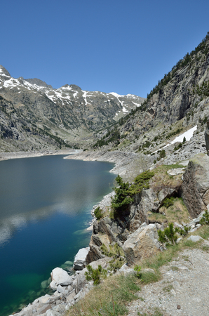 trampled: A pathway is trampled along the mountain artificial lake (Embassament de Cavallers) in the Spanish Pyrenees.