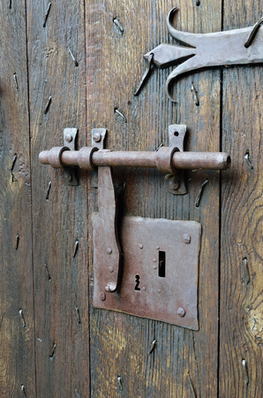 batten: The old-style big metal lock with a latch on the wooden surface of the ancient batten door