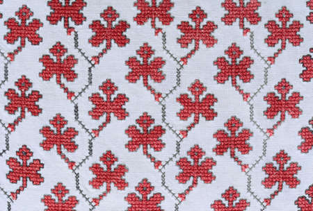 cross stitch: The old-fashioned handmade embroidery is photographed closely. The net of floral motives is made by cross stitch on the homespun cloth.