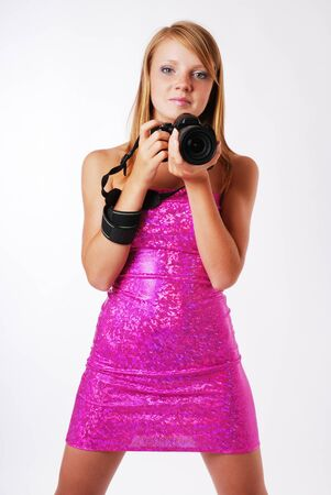 teenage girl dress: An teenage girl is holding with DSLR and looking at camera. She is wearing a pink strapless dress. The blonde is standing with her legs apart.