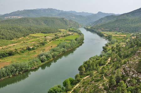 Fertile valley of the river Ebre is photographed from above in spring. There are many fields and plantations, a large forest on the remote mountains.