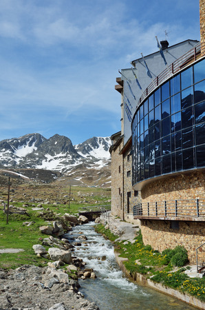 torrent: A torrent is running along the modern buildings on the green slope in the Andorran town El Pas de la Casa. The spring mountains are reflected in the glass wall.