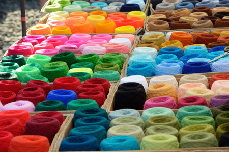 Many bobbins of motley acrylic textile fibers are gathered together.