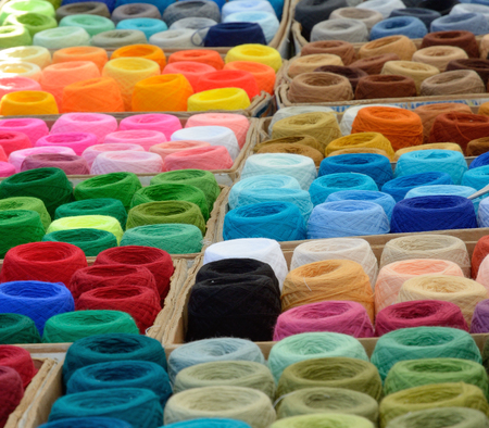 synthetic fiber: Many bobbins of motley acrylic textile fibers are gathered together.