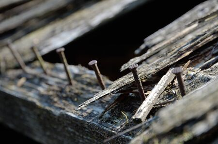 The rusty nails stick out the old wooden board.