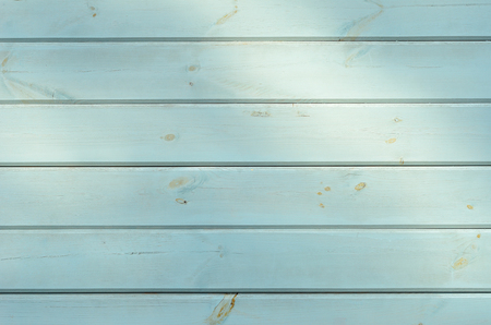 horizontally: A wall is horizontally made of the wooden boards stained. There are the spots of sunlight.