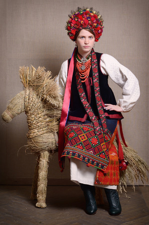 strip shirt: The young woman is sitting on the straw bull. She is wearing a Ukrainian traditional garment of wedding.