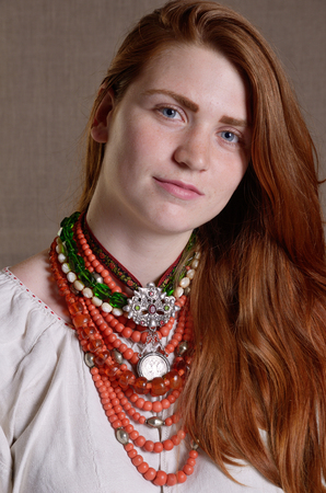 ukrainian ethnicity: The modern young woman is wearing a Ukrainian typical embroidered shirt, multiple necklaces with a pendant.