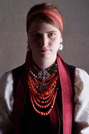 strip shirt: The modern young woman is wearing Ukrainian traditional garment with the multiple necklaces and a pendant.