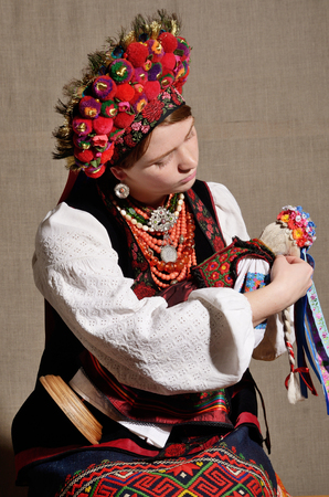 ukrainian ethnicity: The modern young woman is wearing a Ukrainian traditional garment. She is playing with a rag doll. Stock Photo