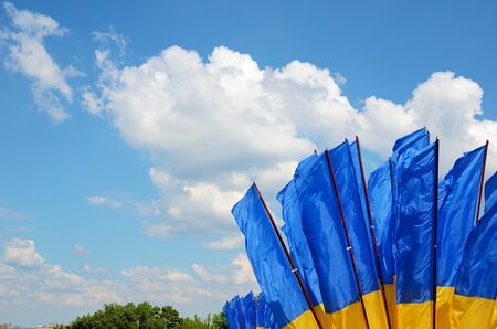 fluttering: Yellow-blue national banners are fluttering on the wind against the blue sky with white clouds. Stock Photo