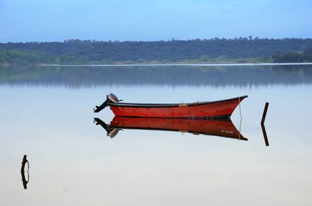 The stationary boat with an engine is reflected in the specular water surface of the pond. It is fixed with vertical post at the shallow.